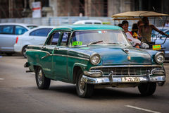 old vintage classic taxi car driving on Cuban Havana city street with people in background Stock Photo