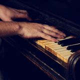 Old vintage classical black piano with male hand playing on it i. N dramatic light on dark background. Closeup toned portrait Royalty Free Stock Image