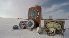 Old vintage clock collection on winter snow in field and clouds, time lapse 4K stock video footage