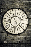 Old vintage clock in monochrome on textured brick wall Stock Photo