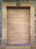 Old and vintage closed window with wooden shutter in a granite stone wall and blue tiles, with number 40 on top royalty free stock image