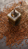 Old vintage coffee grinder on roasted hot beans with smoke Stock Photography