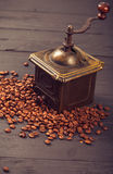 Old vintage coffee mill on roasted hot beans Stock Images