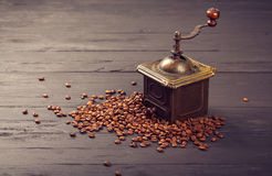 Old vintage coffee mill on roasted hot beans Royalty Free Stock Photography