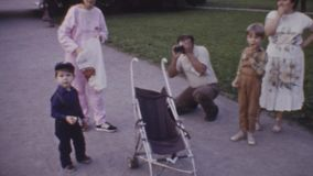 Old vintage color film man taking photo of kid walking with family in city park. Old vintage color film man taking photo of little kid in blue cap walking with stock video