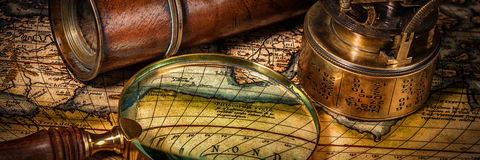 Old vintage compass on ancient map. Travel geography navigation concept background - letterbox panorama of old vintage retro compass with sundial, spyglass and Stock Image
