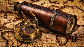 Old vintage compass on ancient map. Travel geography navigation concept background - panorama of old vintage retro compass with sundial and spyglass on ancient Stock Images