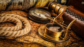 Old vintage compass on ancient map. Travel geography navigation concept background - panorama of old vintage retro compass with sundial, spyglass and rope on Stock Image