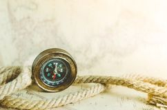 An old vintage compass and a rope on a map with a ray of sun falling on it. Vintage old compass and rope on the background of an old map from the incident light Royalty Free Stock Photos