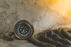 An old vintage compass and a rope on a map with a ray of sun falling on it. Vintage old compass and rope on the background of an old map from the incident light Royalty Free Stock Image