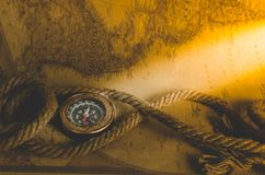 An old vintage compass and a rope on a map with a ray of sun falling on it. Vintage old compass and rope on the background of an old map from the incident light Royalty Free Stock Photo