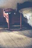 Old vintage cradle in chamber. Vintage cradle in old village house chamber on wooden floor at bright window royalty free stock photography