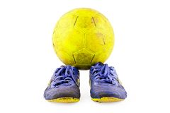 Old vintage damaged futsal sports shoes and ragged yellow ball on white background football object isolated