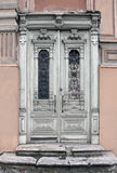 Old vintage door of an historic building. Old vintage door of an historic building with carved wooden decorations painted in white. Vilnius, Lithuania Royalty Free Stock Photography