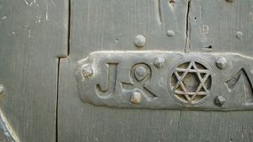 Old vintage door with Star Magen or Shield of David. Old door with Star Magen or Shield of David into a steel frame placed on textured colorful old wood in Haut stock video footage