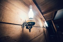 Old vintage electric lamp on wooden wall. Royalty Free Stock Images