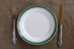 Old vintage empty plate with a green border. On a burlap background. Fork and knife lying near plate. View from above Stock Images