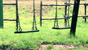 Old vintage empty swings with chains swaying at playground for child, moved from wind, slow motion vintage style stock video