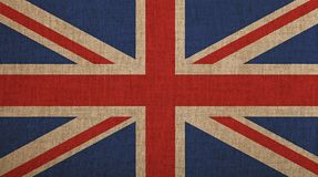 Old vintage faded UK Great Britain flag over canvas. Old grunge vintage dirty faded UK Great Britain national flag over background of jute linen canvas Stock Image