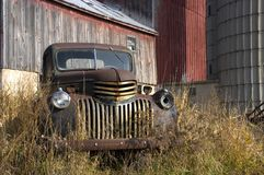 Old Vintage Farm Truck by Barn. Old farm truck quietly sitting by the barn and silo royalty free stock image