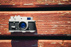 Old vintage film photo camera lying on wooden background. Copy space. Top view Stock Images