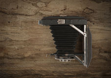 Old vintage folding camera on wood Stock Photography