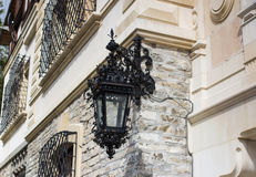 Old vintage forged lantern at front side of an ancient medieval castle. Old vintage forged lantern at facade front side of an ancient medieval Peles Castle at Stock Photography
