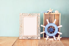 Old vintage frame with naurical wheel on wooden table. vintage filtered image Stock Images