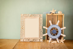 Old vintage frame with naurical wheel on wooden table. vintage filtered image royalty free stock photography