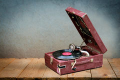 Free Old Vintage Gramophone Player With A Vinyl Record In It In A Dark Red Case On Wooden Table Against Old Grunge Wall Royalty Free Stock Photography - 96083837