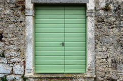 Old vintage green doors in a stone wall fence. Royalty Free Stock Image