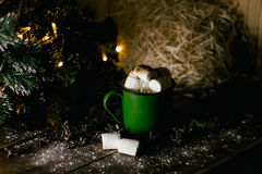 An old vintage green mug with cocoa and marshmallows on the Christmas lights background. On the wooden surface royalty free stock images