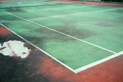 Old and vintage of green tennis court, The field line and corner of court. Dirty ground of tennis court Stock Photos