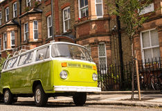 Old vintage green van parked in a street with victorian houses. In the background stock photography