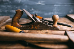Old vintage hand tools on wooden background. Carpenter workplace. Stock Photo