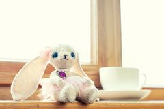 Old vintage handmade art plush Rabbit doll toy. Handmade colorful vintage small art teddy doll toy-Rabbit sitting on window sill with cup of tea. Multicolored Royalty Free Stock Image