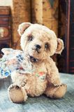 Old vintage handmade favourite Teddy bear toy from childhood. Old vintage handmade small Teddy Bear toy with bow. Indoors multicolored vertical image with retro Royalty Free Stock Images