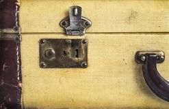 Old vintage hard yeallow suitcase with latch lock and handle tor Stock Photography