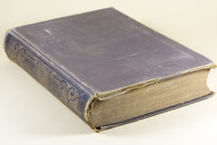 Old vintage hardcover book. With a tattered cover and binding and discolored pages lying on a neutral background viewed corner on Stock Photo