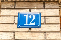 Old vintage house address blue metal number 12 twelve on the brick facade of residential building exterior wall on the street side stock photo