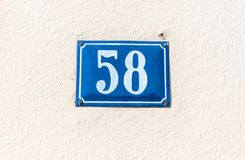Old vintage house address blue metal plate number 58 fifty eight on the plaster facade of abandoned home exterior wall on the stre stock images