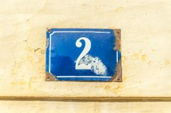 Old vintage house address blue metal plate number 2 two on the plaster facade of abandoned home exterior wall on the street side royalty free stock photos
