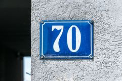 Old vintage house address metal number 70 seventy on the plaster facade of abandoned home exterior wall on the street side.  Royalty Free Stock Image
