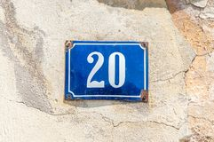 Old vintage house address metal number 20 twenty on the plaster facade of abandoned home exterior wall on the street side.  stock photography