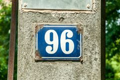 Old vintage house address metal plate number 96 ninety six on the plaster facade of abandoned home exterior wall on the street s stock photography