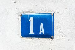 Old vintage house address metal plate number 1 A on the plaster facade of abandoned home exterior wall on the street side stock photo