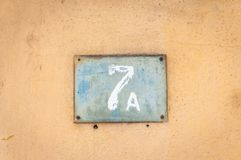 Old vintage house address metal plate number 7 A seven on the plaster facade of abandoned home exterior wall on the street side royalty free stock image