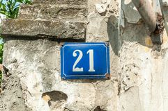 Old vintage house address metal plate number 21 twenty-one on the plaster facade of abandoned home exterior wall on the street s stock photos