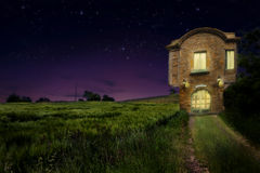 A old vintage house beside wheat field with warm light inside at night Royalty Free Stock Photo