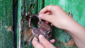 Old vintage iron lock on the door with green paint peeled. Female hand opens and closes lock. Old vintage iron lock on the door with green paint peeled. Female stock video footage